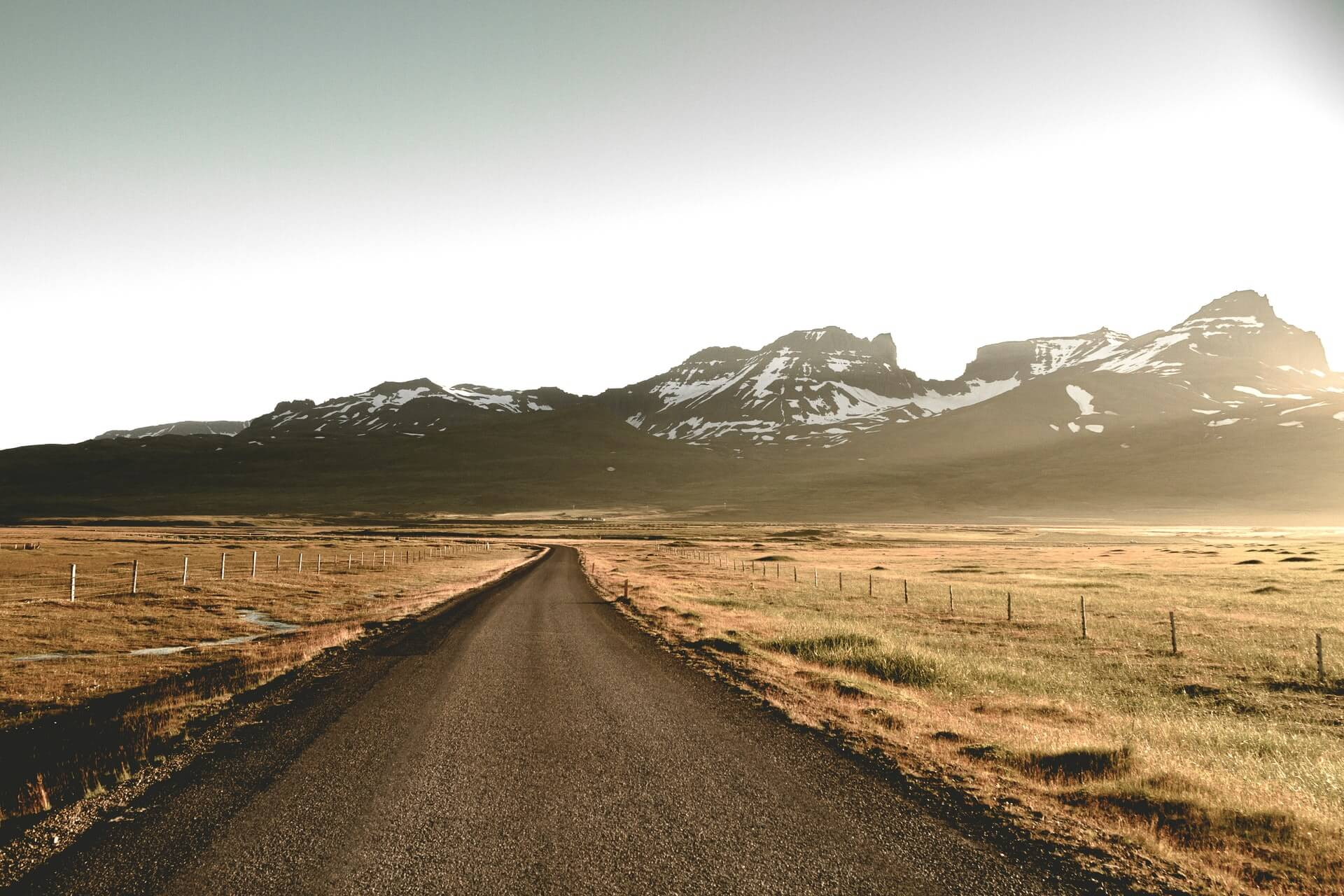 An open road, running past some fields with mountains in the distance
