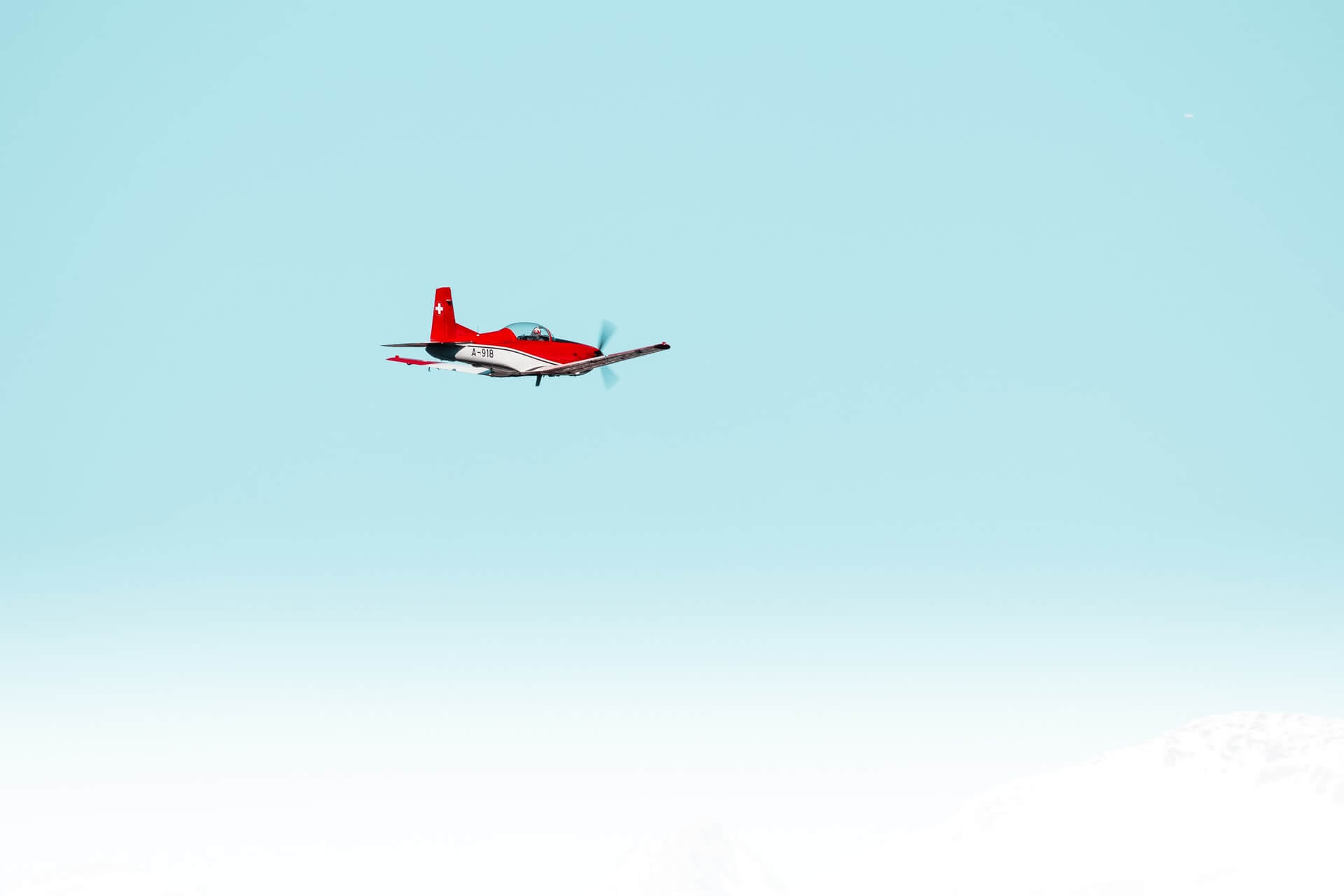 Red plane flying in clear skies