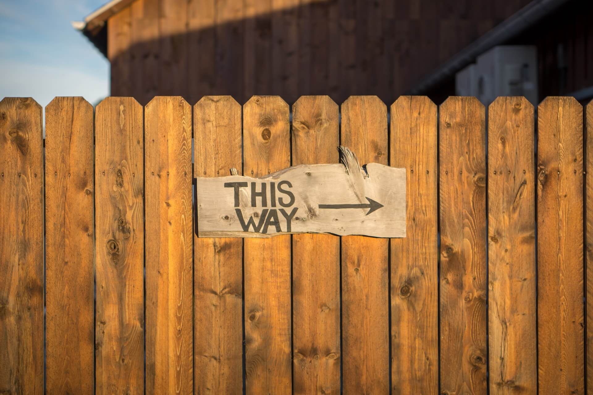 Fence with a 'this way' sign